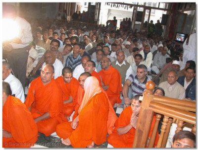 Sants and devotees engrossed in the divine darshan of Lord Swaminarayan during the panchamrut snan