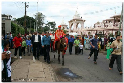 Acharya Swamishree rides a horse to the home of a disciple