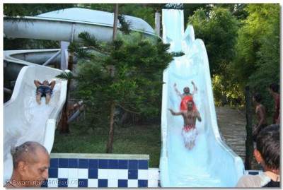 Sants and young children go on the slides beside the pool