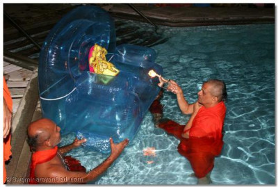 Acharya Swamishree performs the sandhya aarti of the Lord in the pool