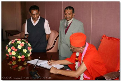 Acharya Swamishree signs the airport VIP Visitors Book