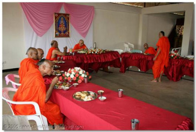 Acharya Swamishree and the sants take some prasad of the Lord
