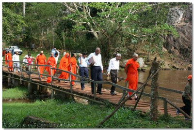 Acharya Swamishree, sants and disciples cross a bridge at the foot of Ssezibwa Falls