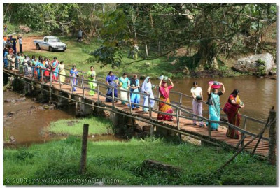 Disciples cross a bridge at the foot of Ssezibwa Falls carrying fruit, to offer to the Lord