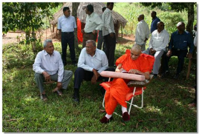 Acharya Swamishree writes mantras as He sits besides the Ssezibwa Falls