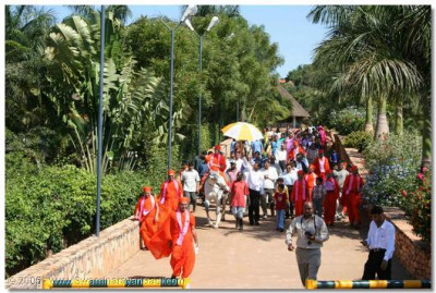 Acharya Swamishree rides through the gardens beside Lake Victoria