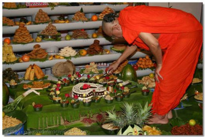 Acharya Swamishree cuts the cake to offer to the Lord
