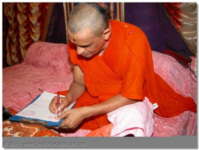 Acharya Swamishree writing mantras during the competition