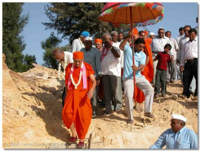 Acharya Swamishree, sants, and devotees head towards the water tank for the opening ceremony in Naranpur