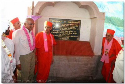 Acharya Swamishree unveils a plaque to commemorate the inauguration ceremony of this water reservoir