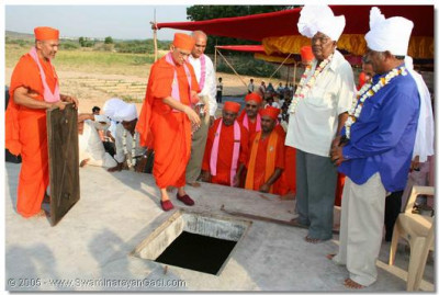 Acharya Swamishree sprinkles some consecrated water into the reservoir