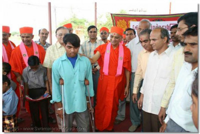 Acharya Swamishree presents crutches to a disabled orphan and gives him the encouragement to excel in life
