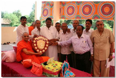 The sporting students of the University in Vaghjipur won a prestigious region competition. The elders of the village and the University present this shield to Acharya Swamishree