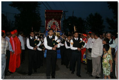 The band leads Acharya Swamishree's chariot towards the temple