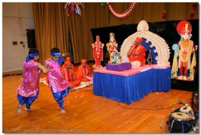 Acharya Swamishree watches young devotees perform