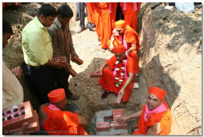 Acharya Swamishree lays the first brick of the new temple