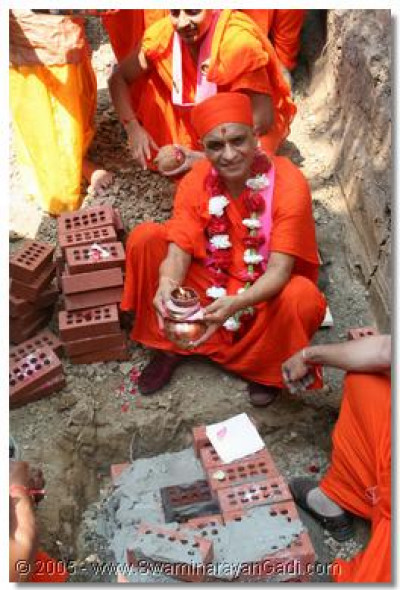 Acharya Swamishree shows the auspicious urn, filled with gold and precious stones, which He then placed in the foundations