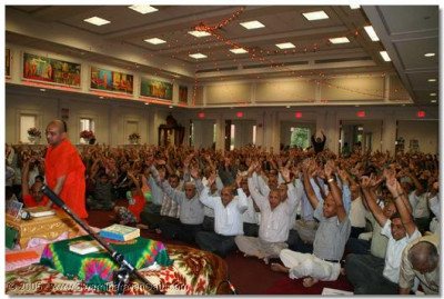 Devotees performing a Jay at the conclusion of Acharya Swamishree's divine aashirwad