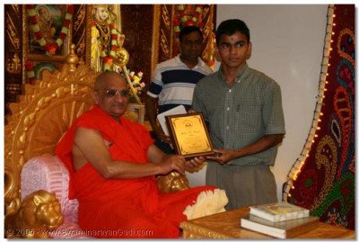 A devotee receives a memento from Acharya Swamishree for giving extensive help in the day to day running of the temple