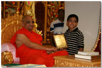A young devotee receives a certificate from Acharya Swamishree for winning the Family Tree competition