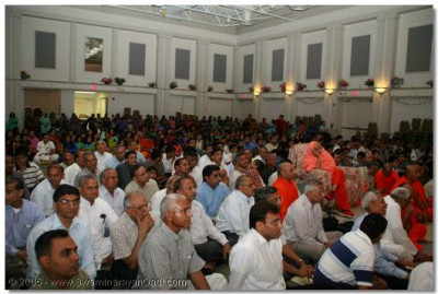 Acharya Swamishree, sants, and devotees watch the performances
