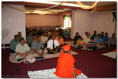A sant recites a passage from the Vachnamrut while the devotees listen