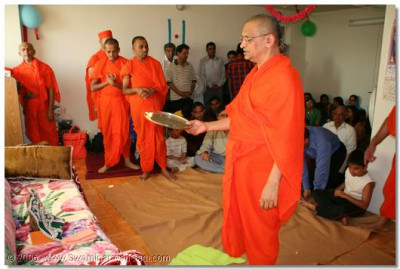 Acharya Swamishree performs the Sandhya aarti at a devotee's home