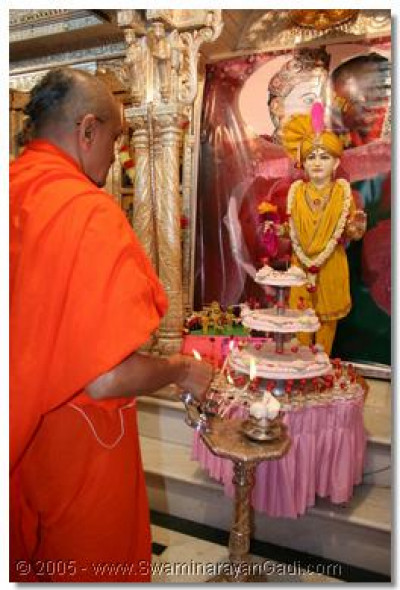 Acharya Swamishree performing aarti to Lord Swaminarayan