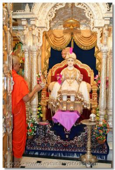 On arrival in Maninagar dham, Acharya Swamishree performs aarti to Lord Swaminarayan