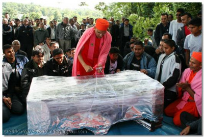 Acharya Swamishree opens a large package offered to Lord SwaminarayanBapa Swamibapa by the devotees of Bolton