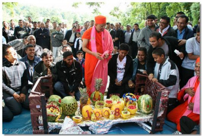 Acharya Swamishree opens a large package containing intricately carved fruit offered to Lord SwaminarayanBapa Swamibapa by the devotees of Bolton