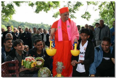 Acharya Swamishree gives darshan with the intricately carved fruit