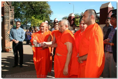 Acharya Swamishree and sant perform aarti during the flag raising ceremony