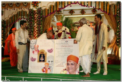 Leading disciples present Acharya Swamishree with a giant birthday card
