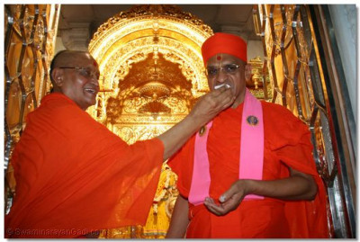 Sadguru Shree Akhileshvardasji Swami offer prasad cake to Acharya Swamishree