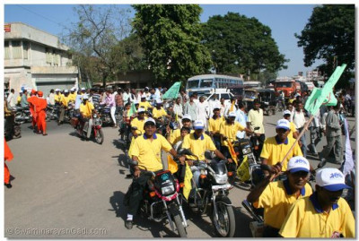 Disciples riding mopeds lead the procession