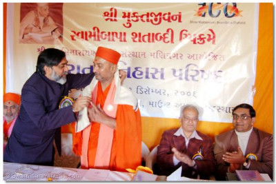 On behalf of the convention organisers and the Gujarat History Parishad, its president shows its appreciation of Shree Swaminarayan Gadi Sansthan by presenting a shawl to Shree Bhagwatpriyadasji Swami
