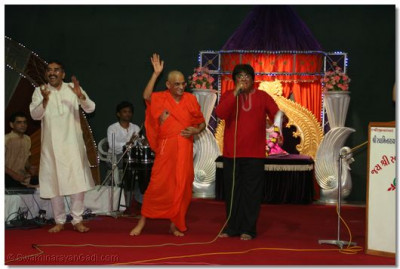 Acharya Swamishree gives darshan during the performance of 'Marak marak hasi bole....'