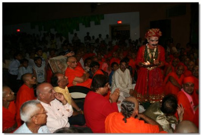 Acharya Swamishree watches as a member of the audience attempts to place the fire in his mouth