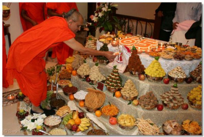 Acharya Swamishree offers Shree Harikrishna Maharaj some prasad cake