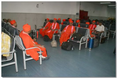 Acharya Swamishree, sants, and disciples wait to board the plane at Chatrapati Shivaji International Airport in Mumbai