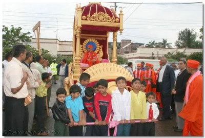 Acharya Swamishree, seated on a chariot, is drawn to the temple steps by young disciples