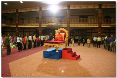 Acharya Swamishree gives darshan on a throne during the raas