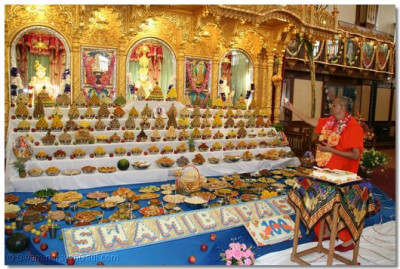 Acharya Swamishree offers the prasad cake to Lord Swaminarayan