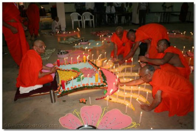 Sants light the candles as Acharya Swamishree gives His darshan