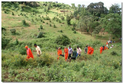 Acharya Swamishree, sants, and devotees trek up a hill