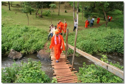 Acharya Swamishree crosses a stream