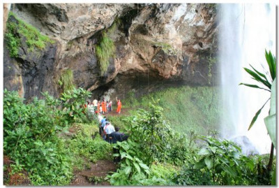 Acharya Swamishree gives darshan near a waterfall