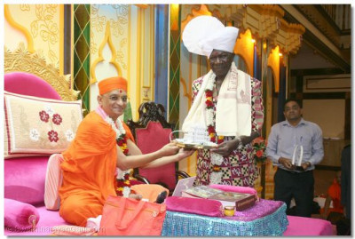 Acharya Swamishree presents a Shree Muktajeevan Swamibapa Smruti Mandir model memento to the Vice President