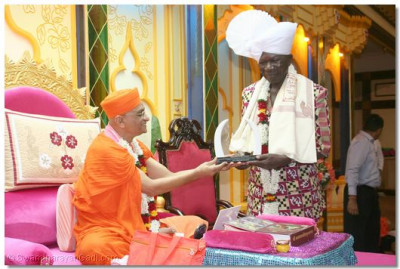 The Vice President accepts a memento from Acharya Swamishree